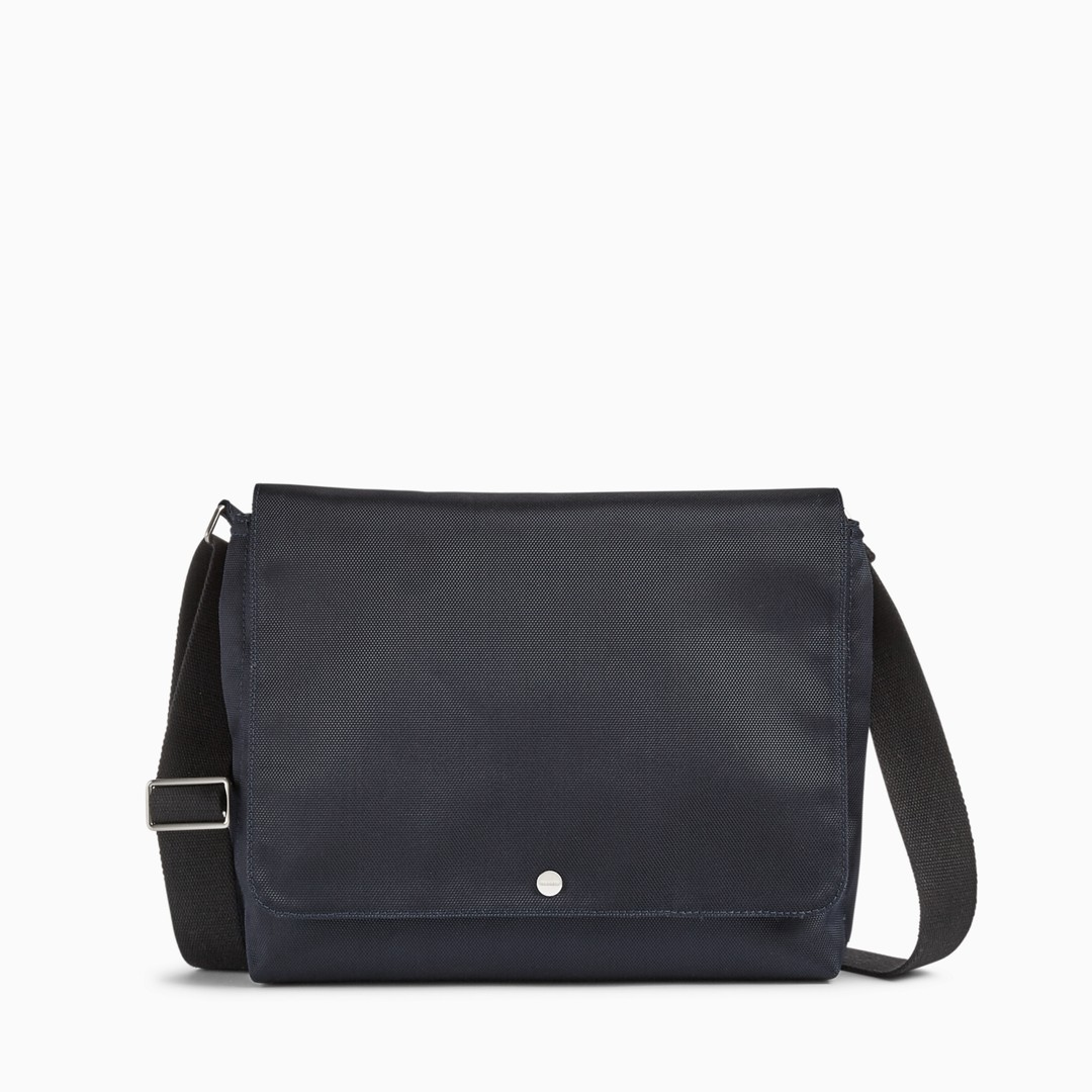 The Eric messenger can be worn comfortably by the adjustable shoulder strap or carried by the grab handle. Two external hidden side zip pockets and a magnet-secured slip pocket on the back provide easily accessible storage. The interior includes a padded sleeve large enough for a 13-inch laptop, a zip pocket, three slip pockets and a pen holder. The flap closure is secured with a magnetic snap.