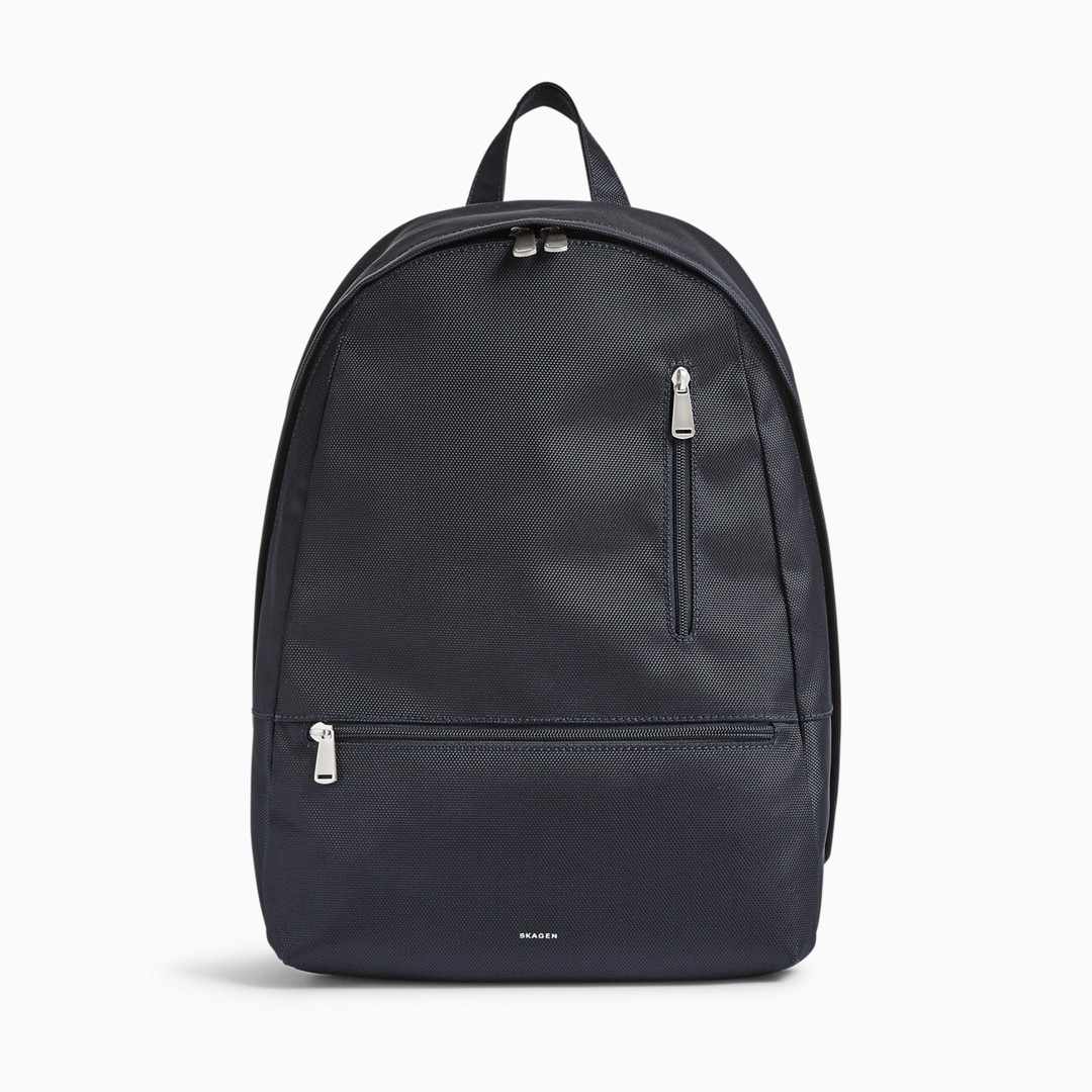 The Krøyer backpack's zip-closure interior features a padded sleeve large enough for a 15-inch laptop along with two slip pockets, two mesh zip pockets and a pen holder. A zippered through pocket on the back allows earbuds to extend through even when closed. The exterior also features easily accessible vertical and horizontal zip pockets. Carry it via the single leather grab handle or by its two adjustable webbing straps.